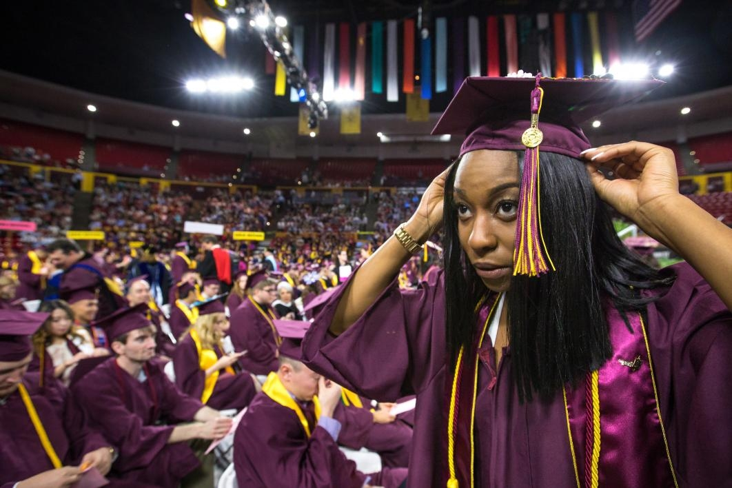 student adjusting graduation cap