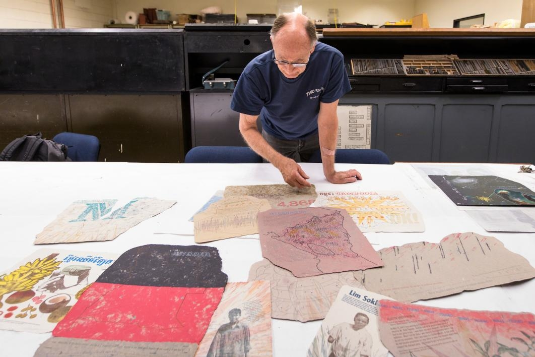 man looking at prints on table