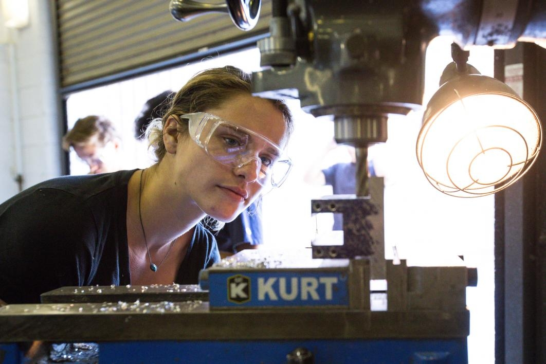 A woman watches the milling of a piece of metal on a drill machine