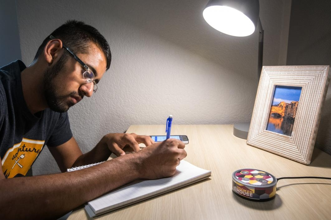 A student takes notes on a desk.
