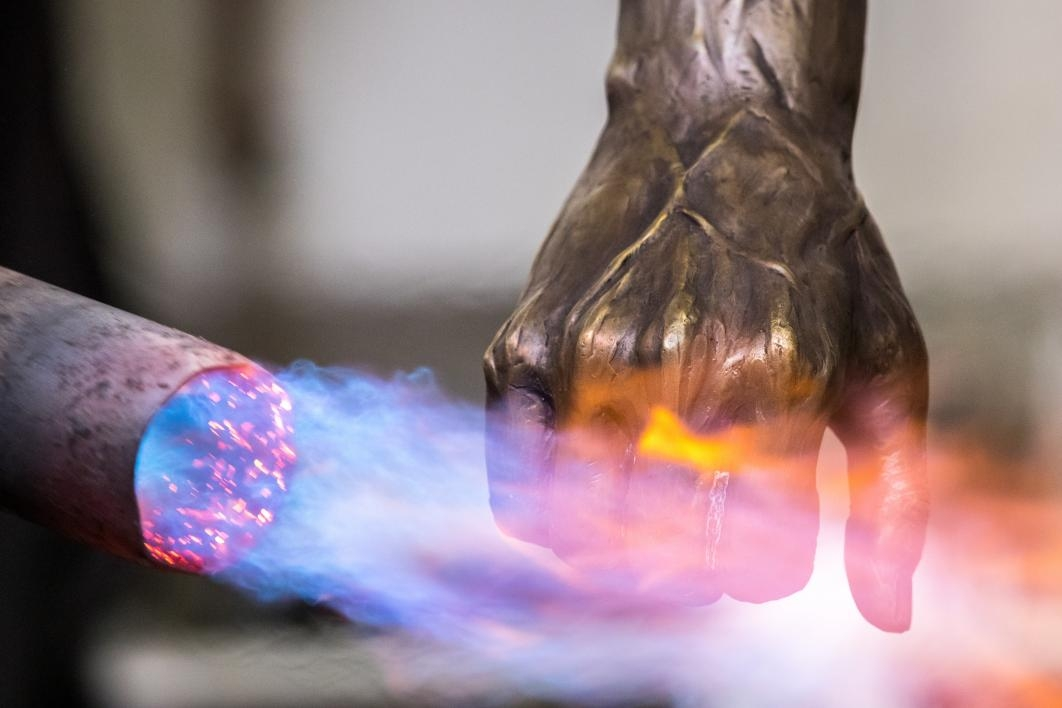 A blowtorch applies a patine to a bronze statue's hand