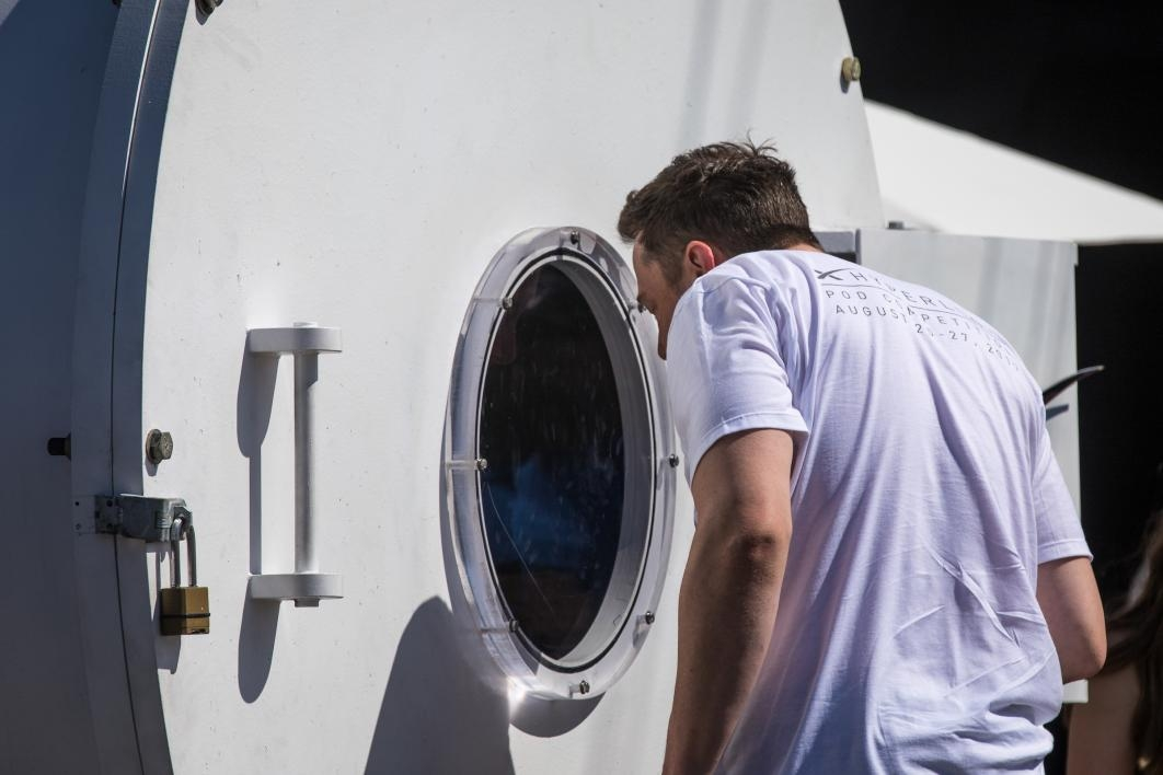 Elon Musk looks into a vacuum chamber