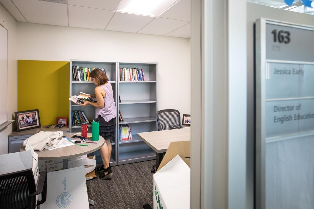 A professor unpacks her books in her new office.