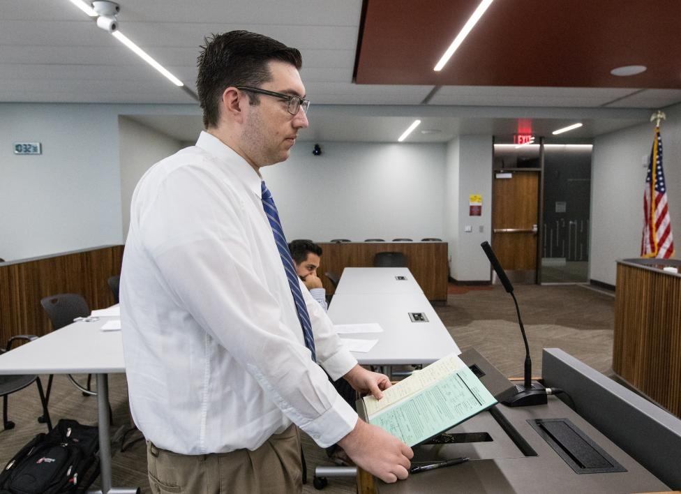 man standing behind podium in moot court