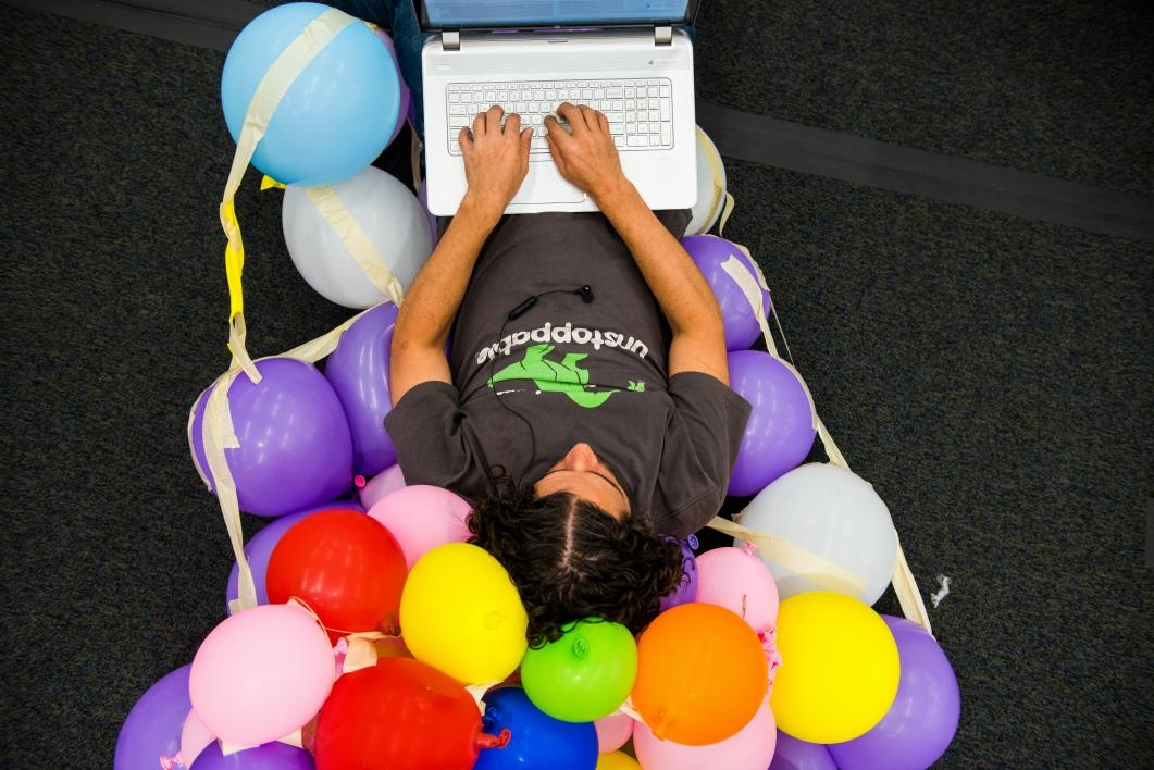 Man sits on a chair of balloons