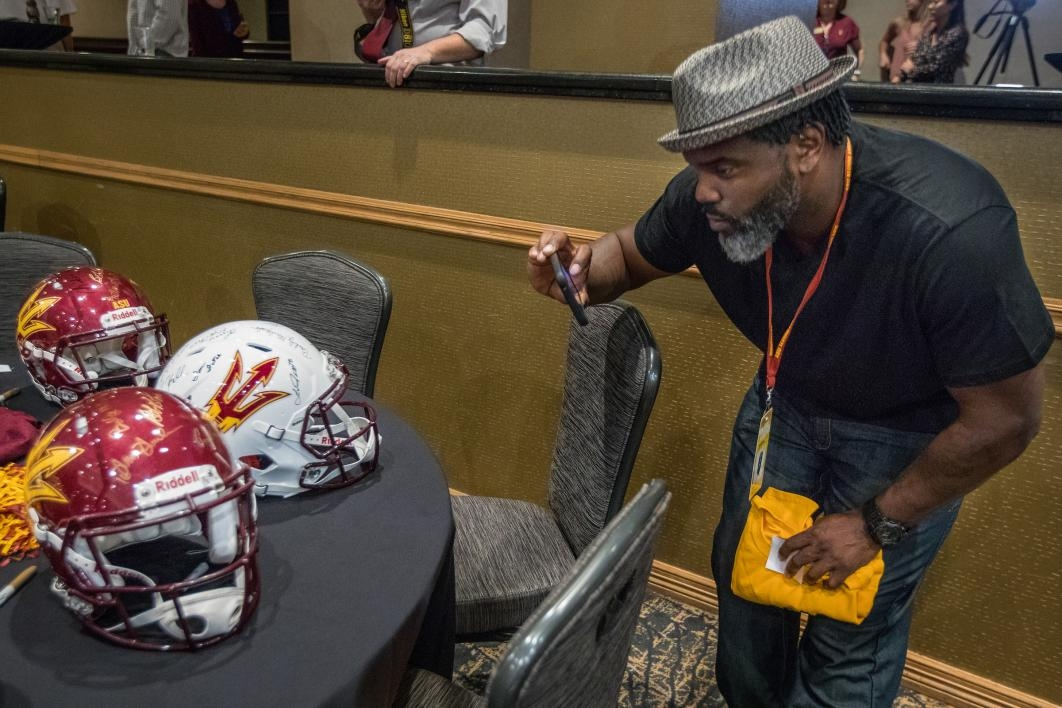 man taking photo of football helmets
