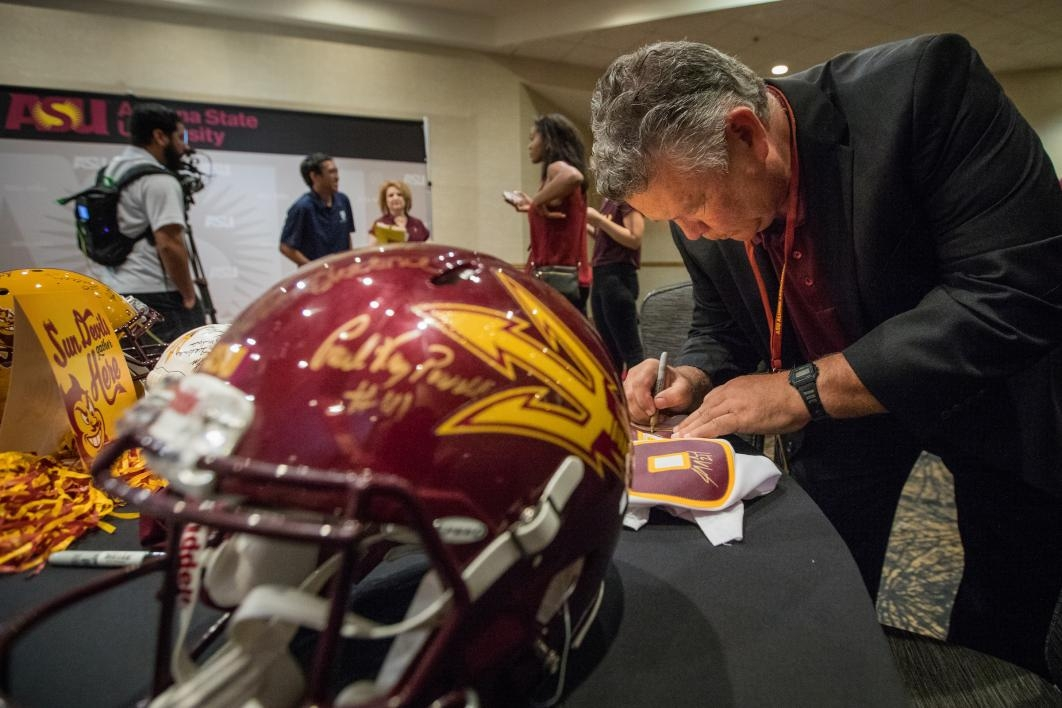 man signing autograph