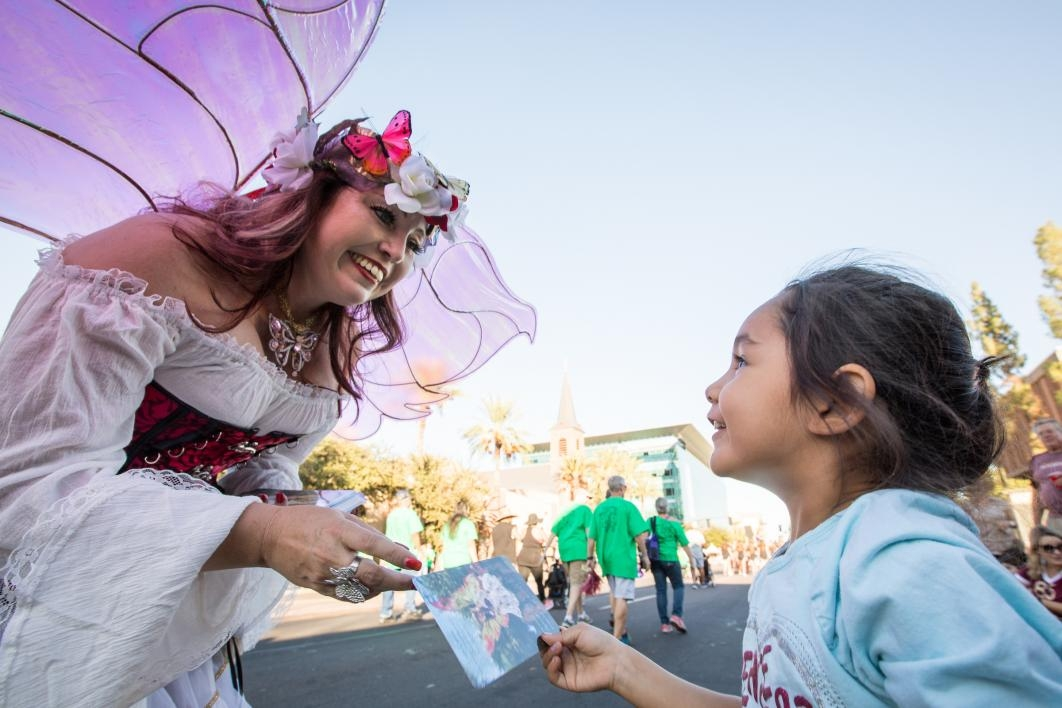 woman dressed as a fairy handing a card to a girl