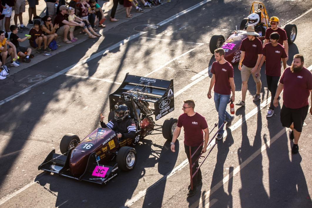 students marching in parade with Formula SAE car
