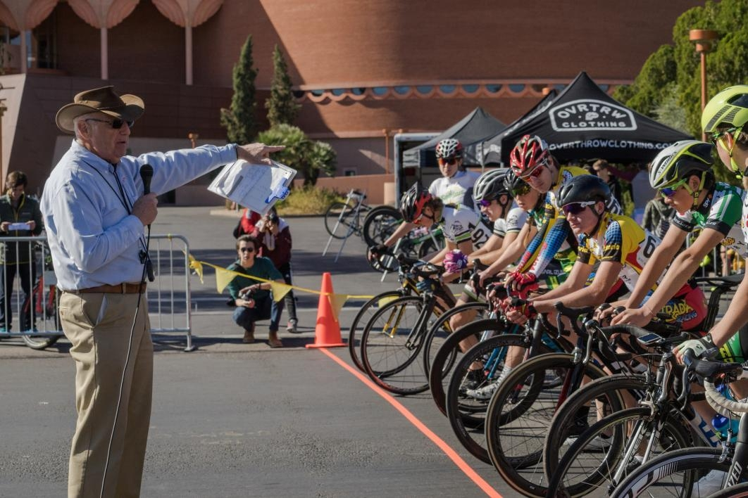 man speaking to bicyclists in race