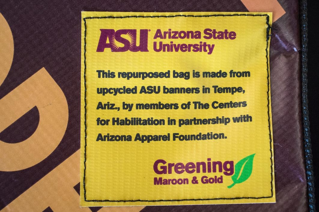 statement on banner bags: This repurposed bag is made from upcycled ASU banners in Tempe, Ariz., by members of The Centers for Habilitation in partnership with Arizona Apparel Foundation
