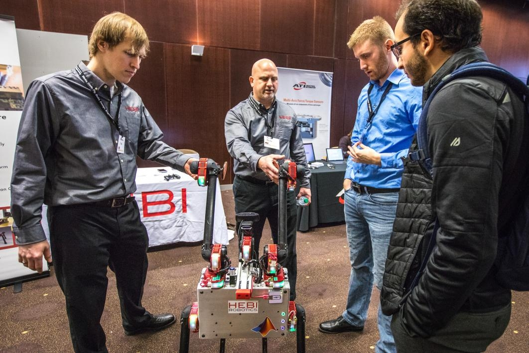 Men demonstrate a robot at a symposium