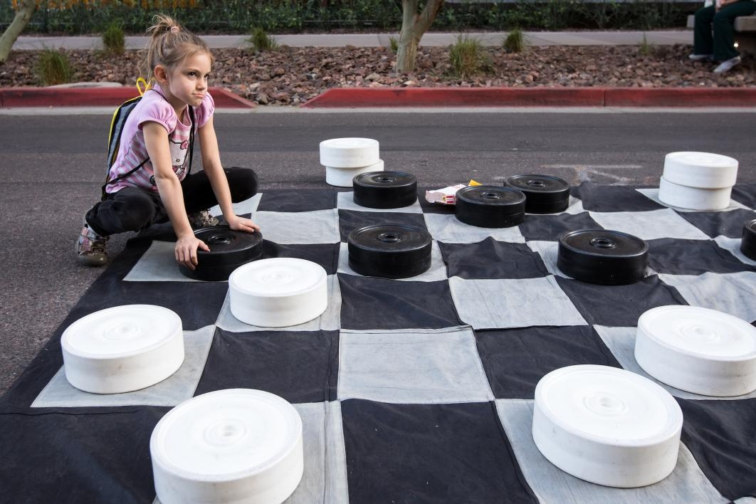 girl playing with giant checkerboard