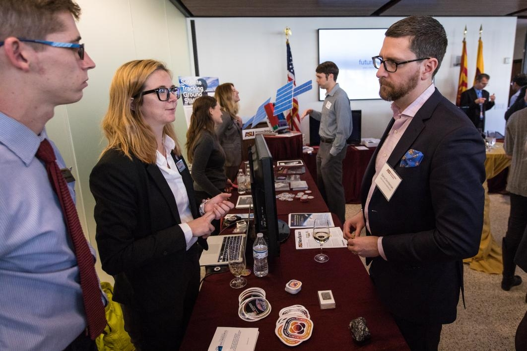 Psyche researchers speak to visitors at a reception