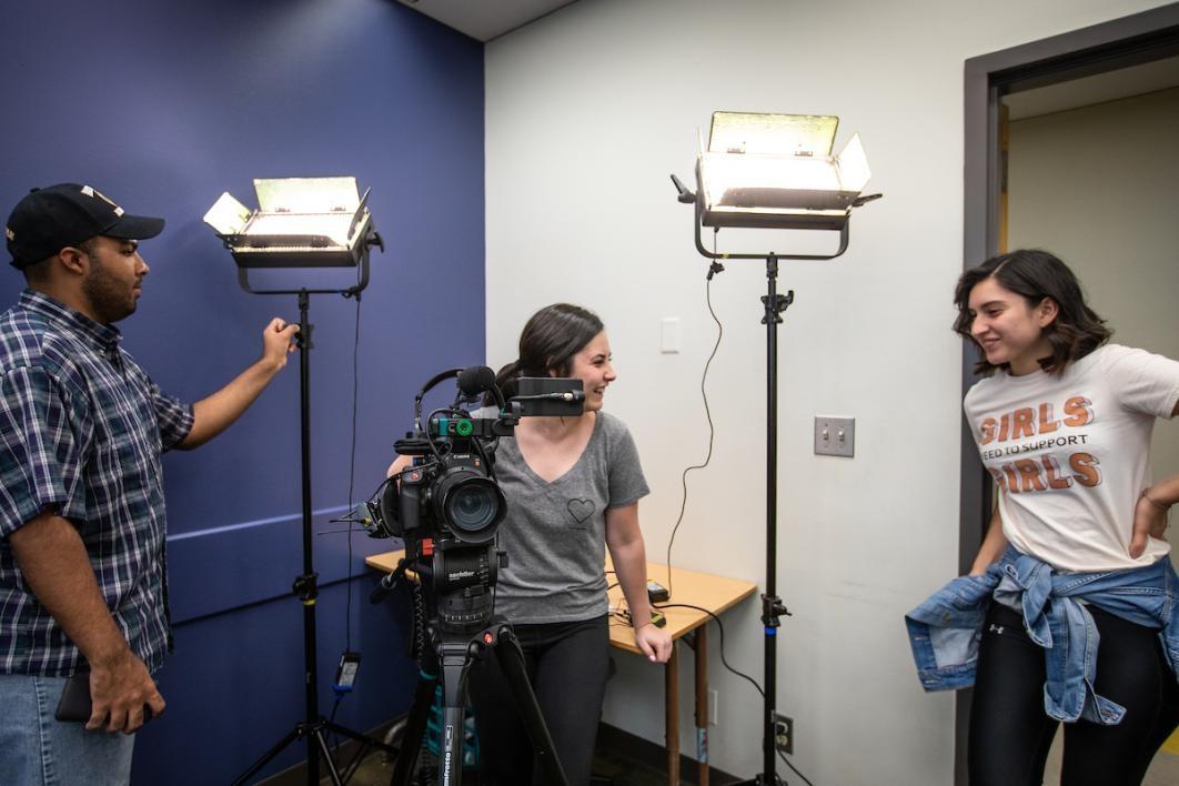 Camera crew lighting up a room