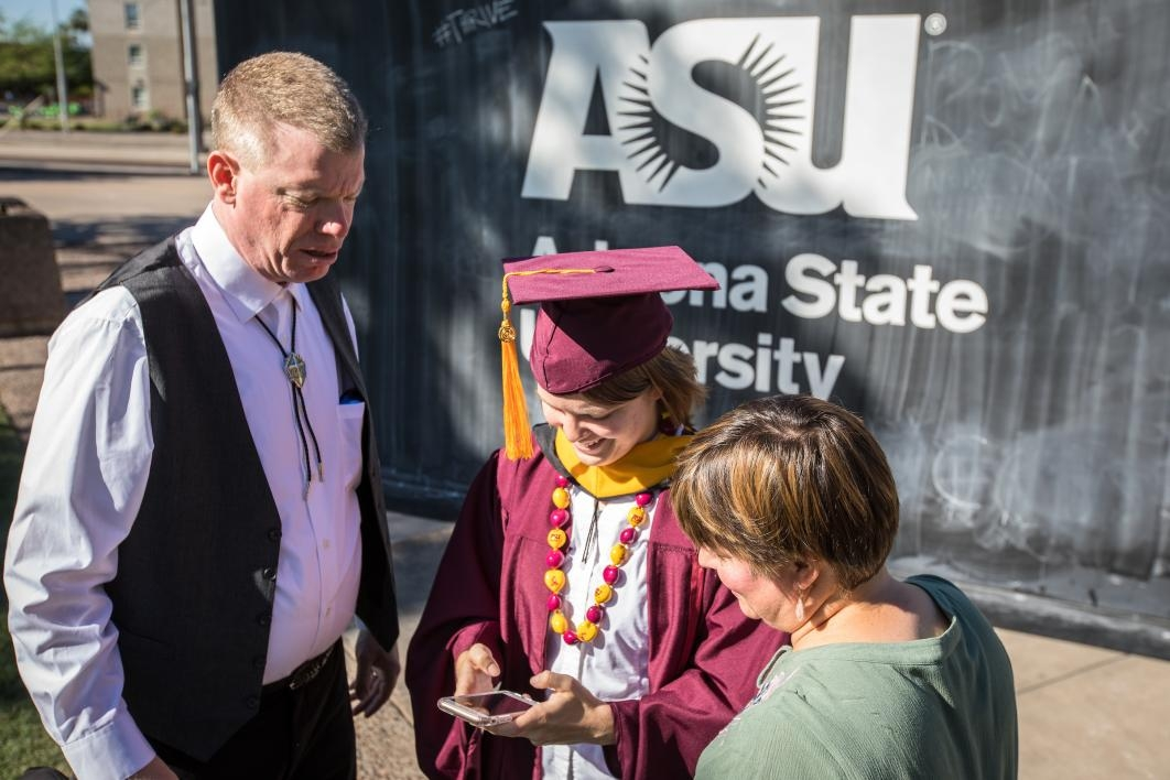 graduate looking at photos on a phone