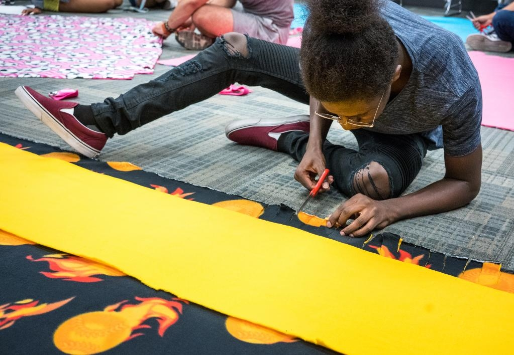 ASU Bridging Success Early Start participant at work on creating a blanket for foster children