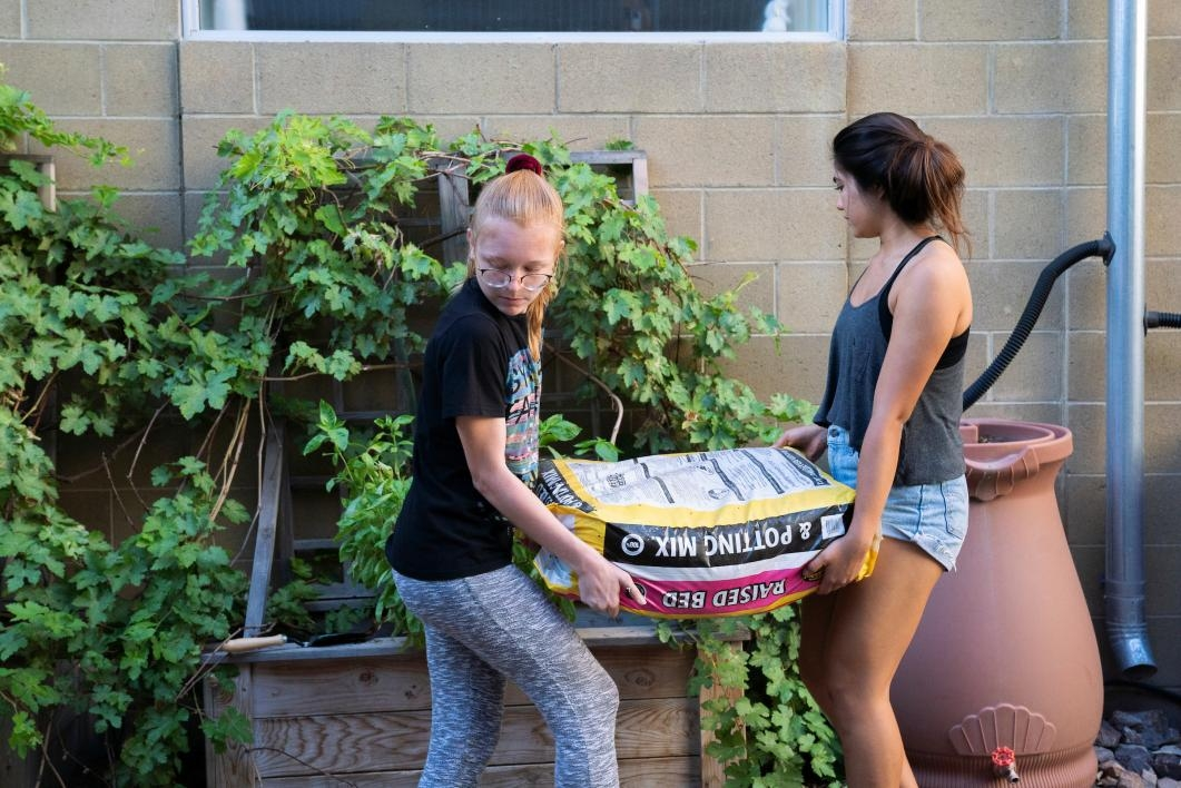 Two girls carry a bag of dirt to a garden