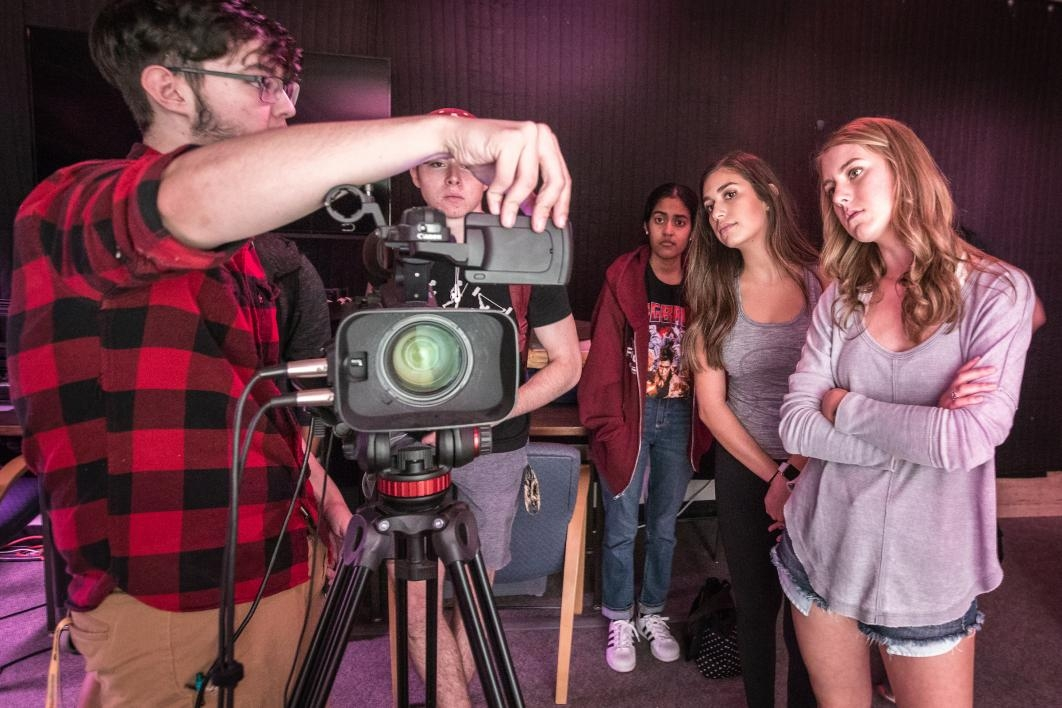 Matt Roman, a student worker at the ASU Library mkrspace, gives a short lesson on the video camera and studio lights to a class of ASU students