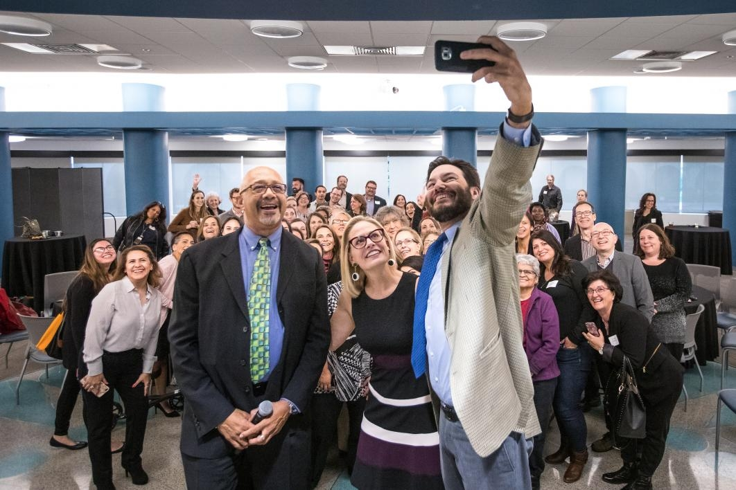 three people taking a selfie in front of a crowd