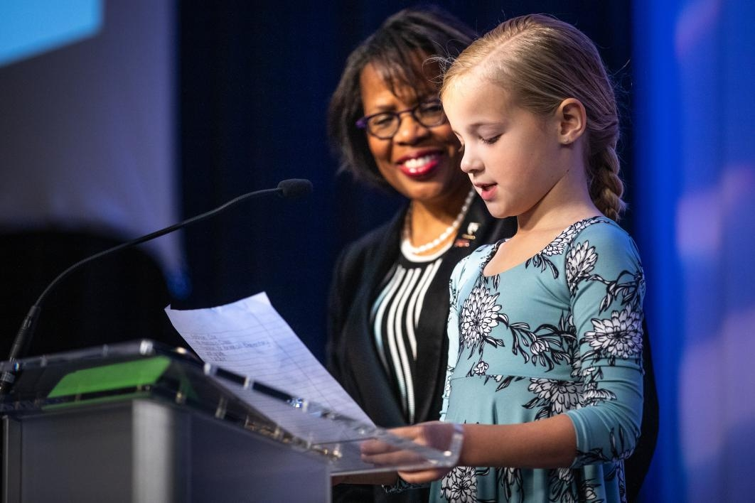 A little girl reads her essay onstage