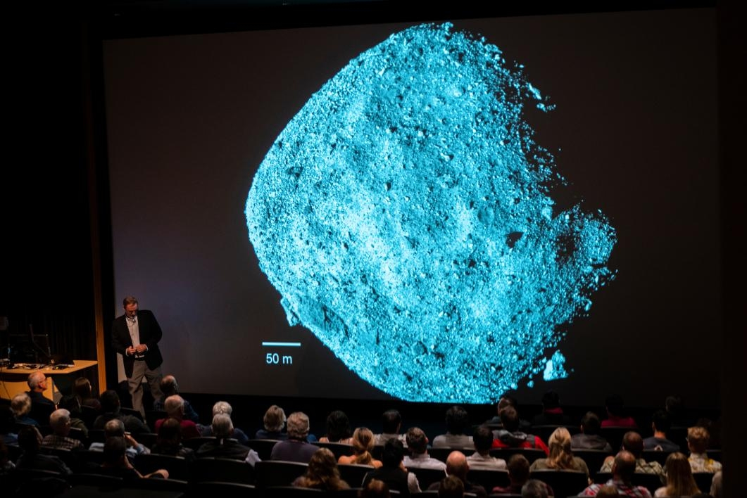 A screen shows the asteroid Bennu to an audience