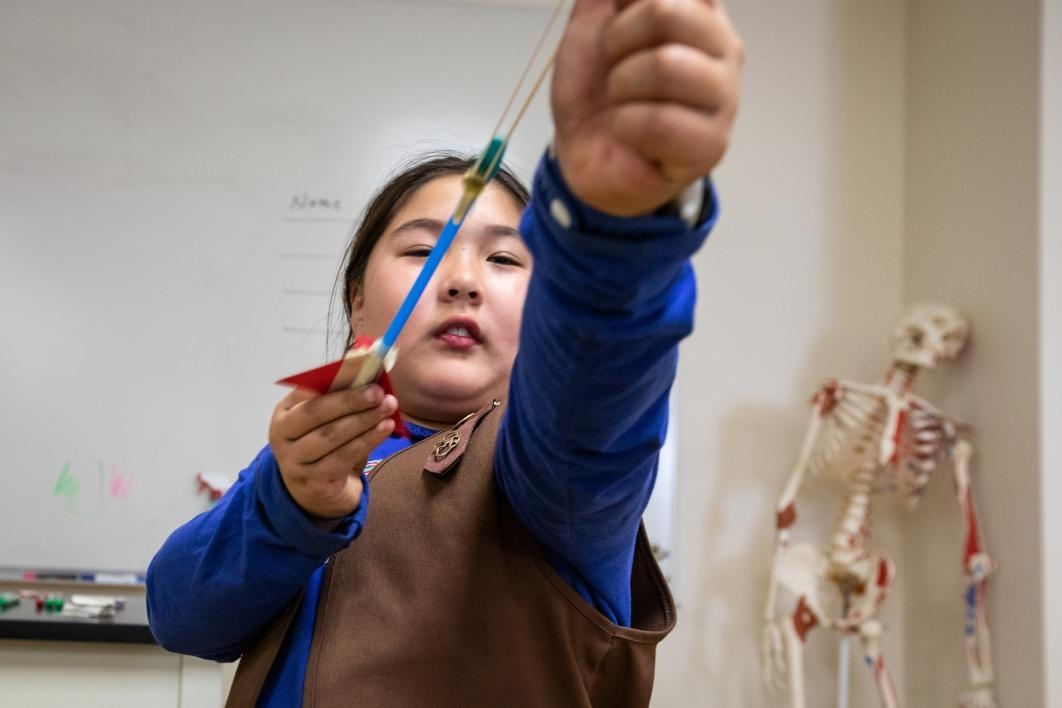 young girl aims a slingshot