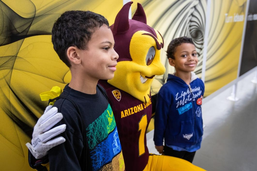 two young boys pose with asu mascot sparky