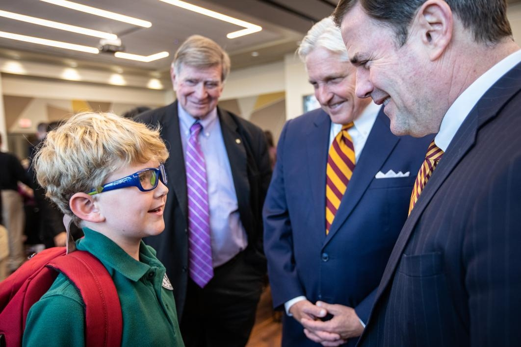 governor Doug Ducey speaks to a child at the greek leadership village opening