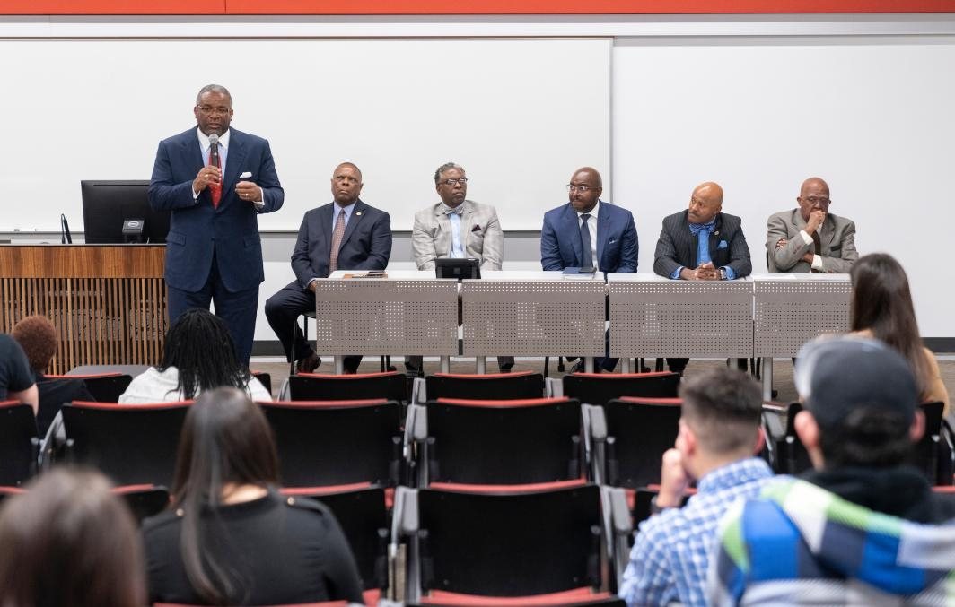 A man speaks in front of a panel