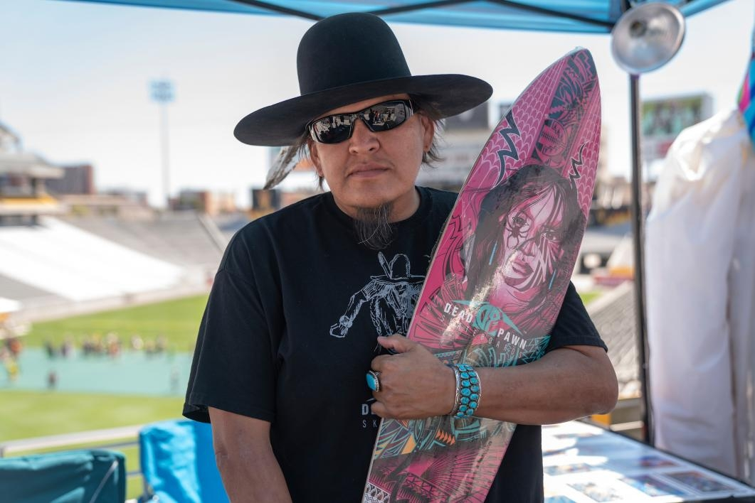 A vendor holds up a skateboard at the ASU Pow Wow