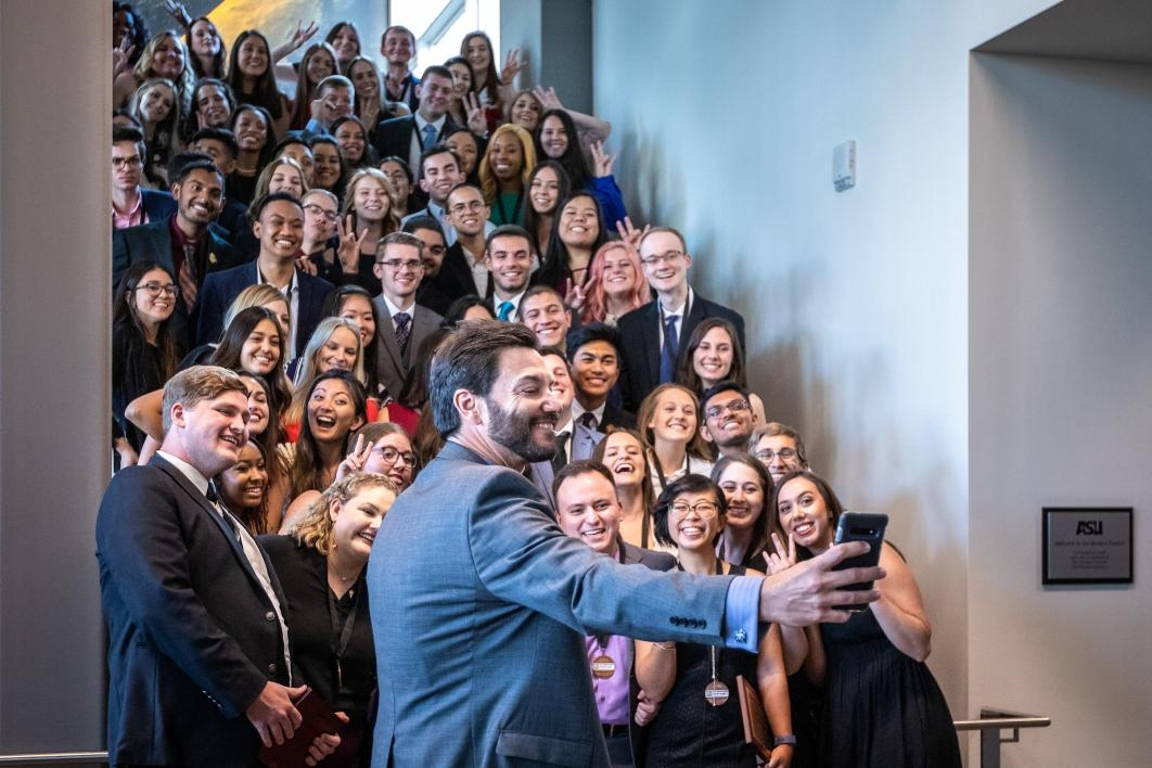 Students gather on a staircase for a group selfie