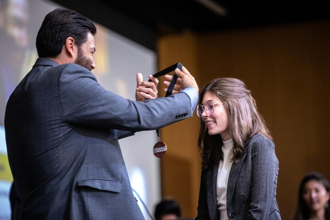 A dean puts a medal on a student