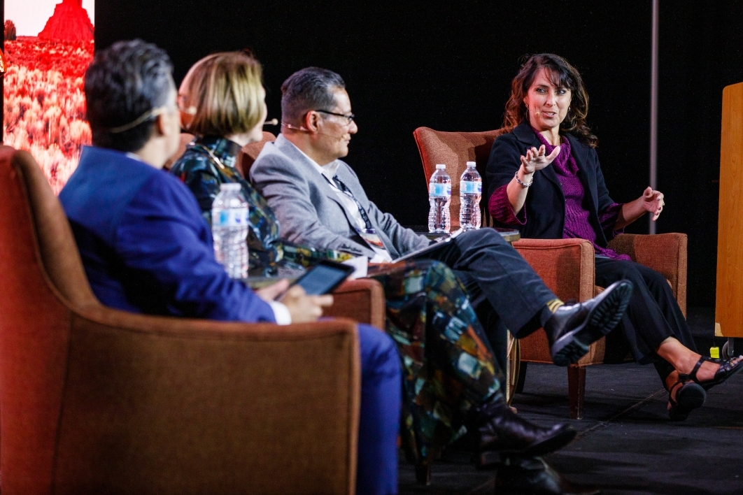 A woman speaks to fellow panel members on a stage.