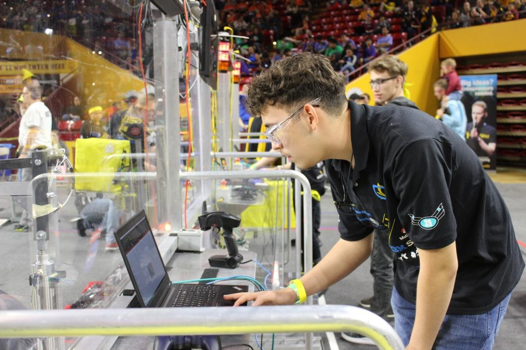 A student looks at a laptop to check on robot controls