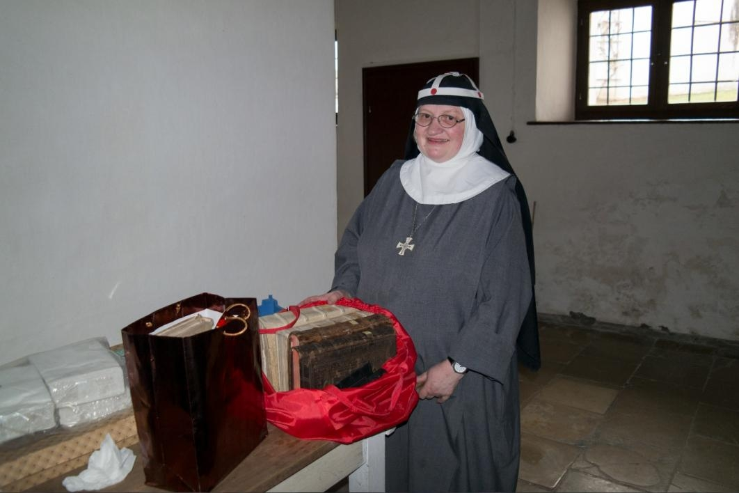 nun next to table full of old books in shopping bags