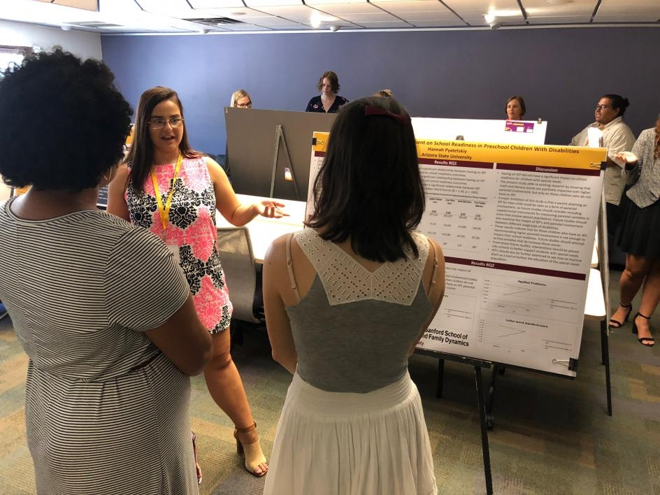 Super fellow presenting her research poster to two faculty.