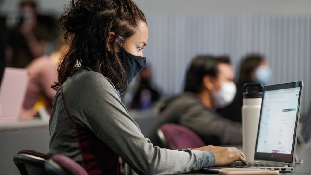 Woman wearing a mask in a classroom while using a laptop