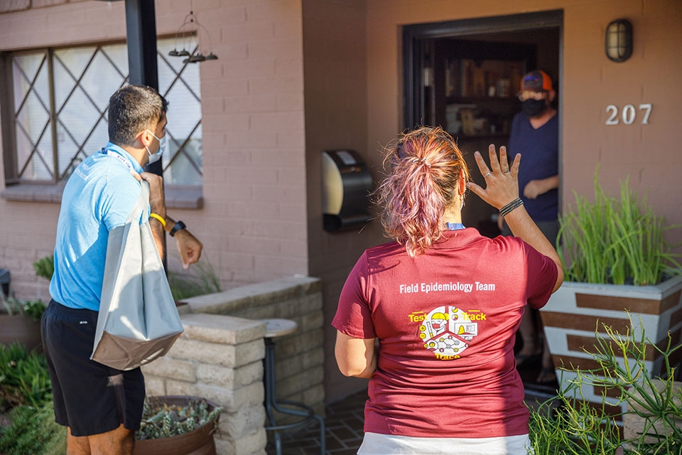 Two volunteers, in blue and maroon shirts, greet a man opening the door to his home.