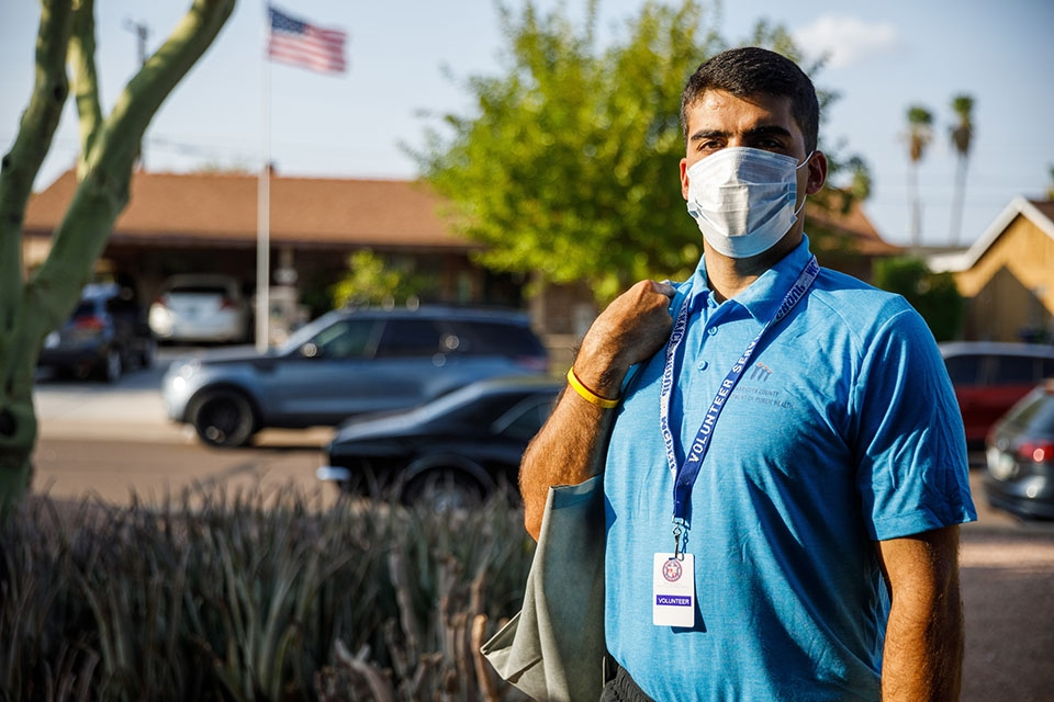 A man wearing a protective mask, a blue shirt and a Maricopa County Department of Public Health volunteer lanyard stands in an Arizona neighborhood.
