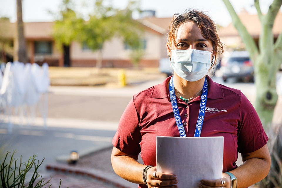 A woman wearing a protective mask, a maroon shirt and a blue lanyard stands in an Arizona neighborhood.