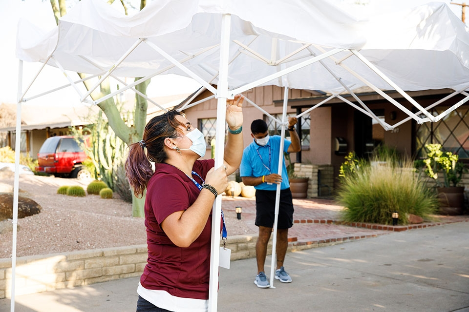 Two volunteers set up a collapsible tent in the driveway of an Arizona home.