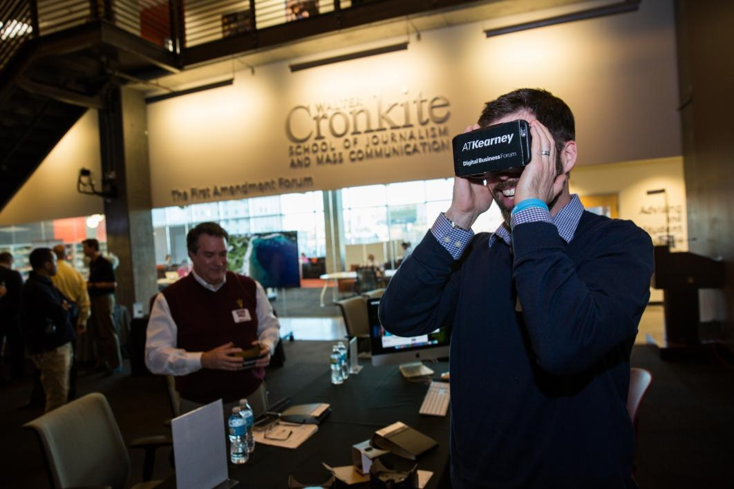 A professor uses a virtual reality device with his phone.