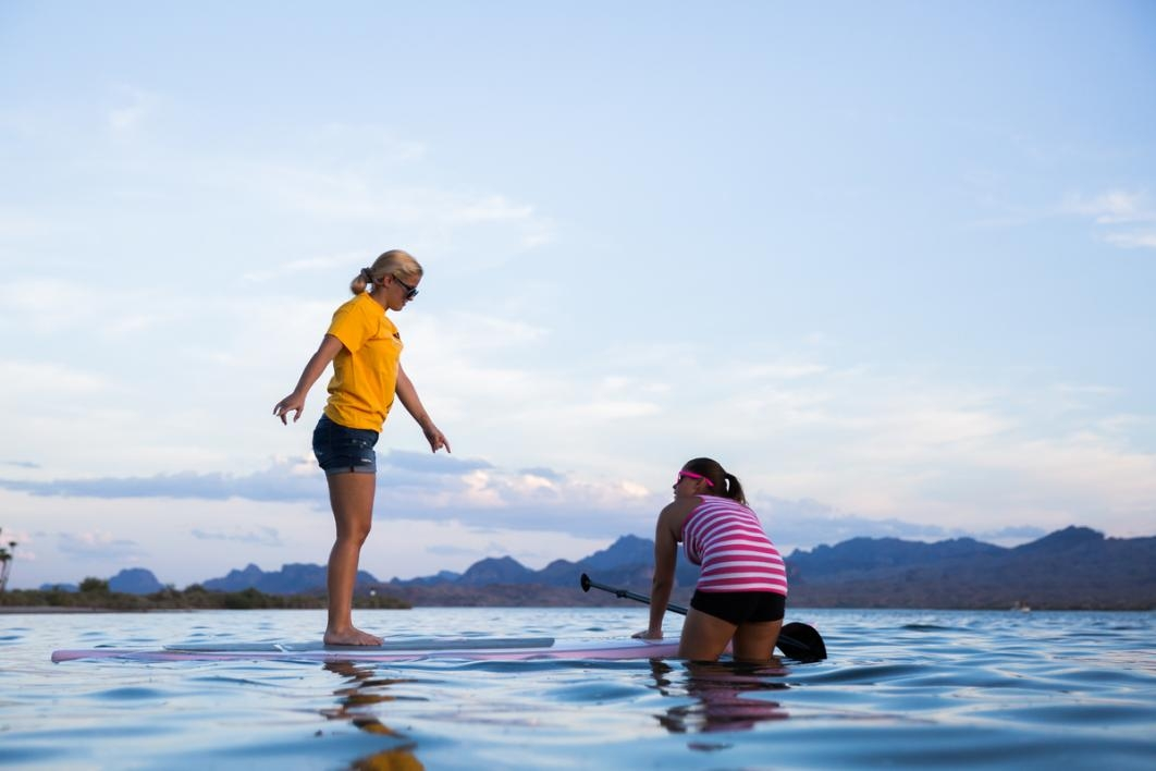 Women getting on a paddleboard.