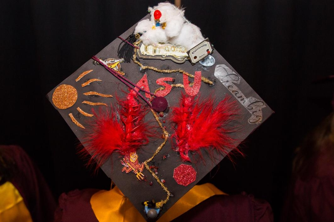 "A graduation cap reads, ""ASU, dream big"" and is accompanied by feathers, glitter and lego men."