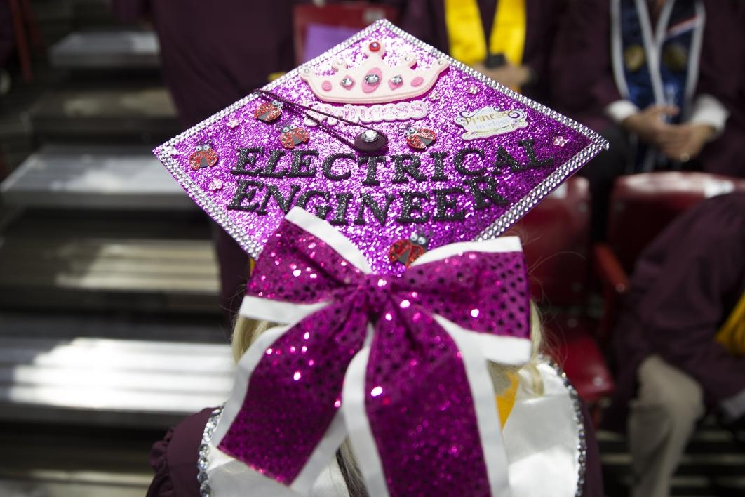 "A graduation cap reads, ""electrical engineer"" in pink and white rhinestones and bows"