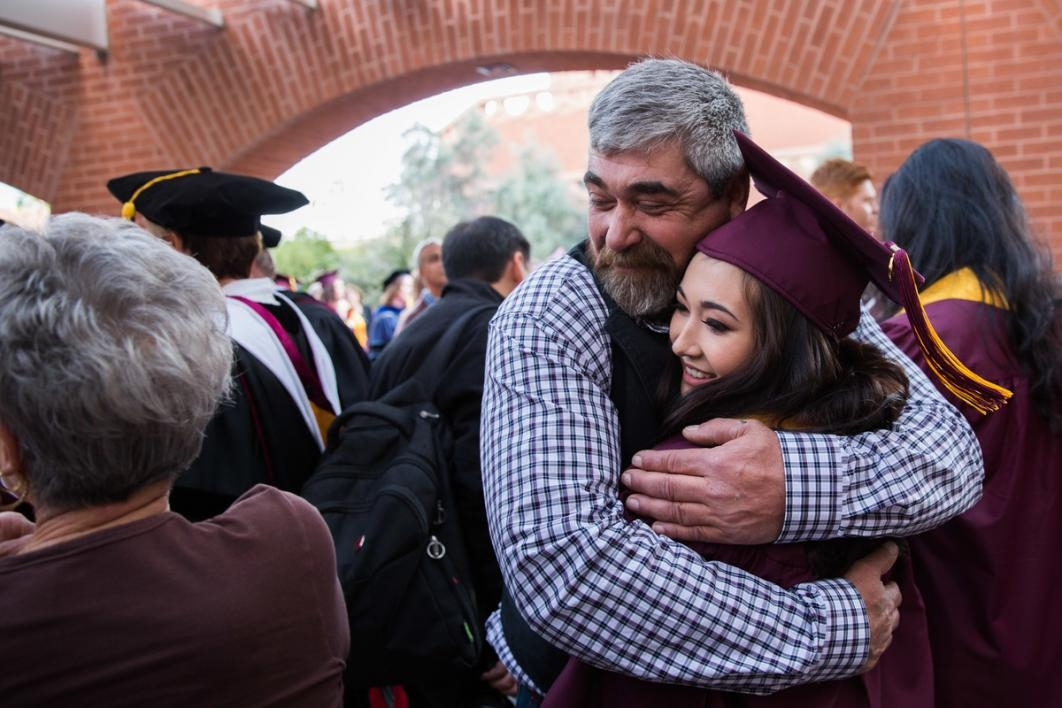 Graduate gets a hug from a man.