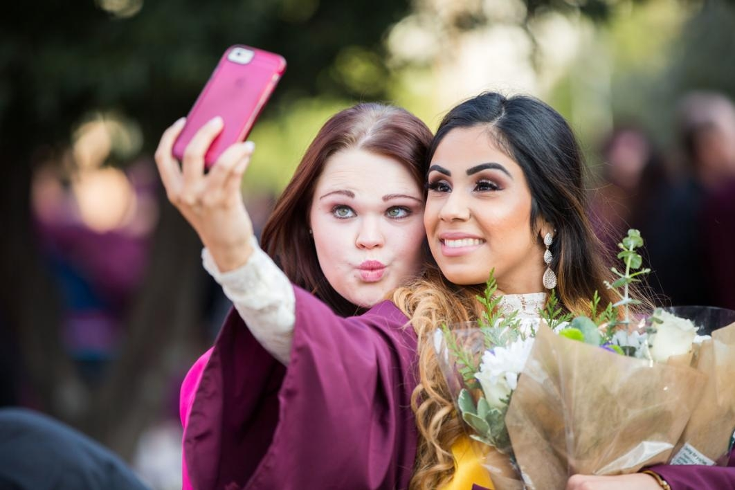 Friends take a selfie during a graduation.
