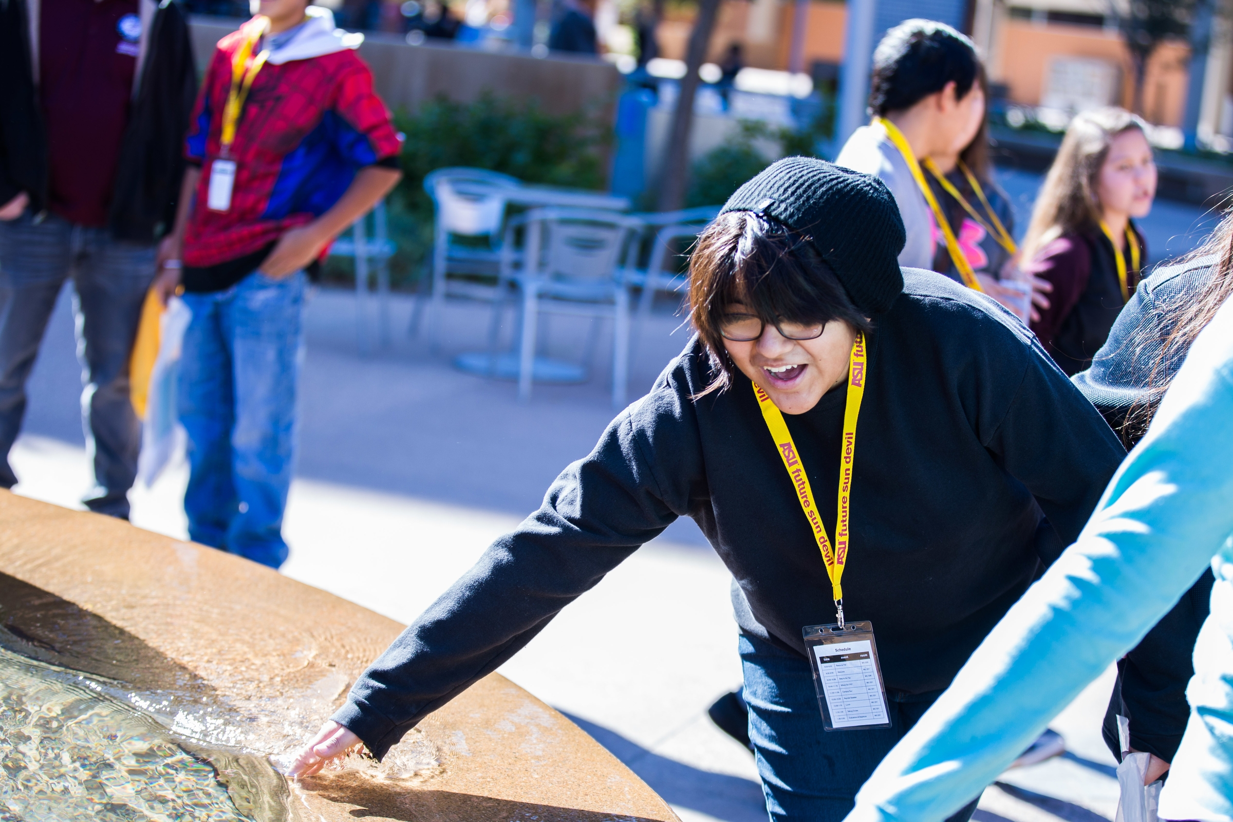 A high schooler splashes his hand in a fountain