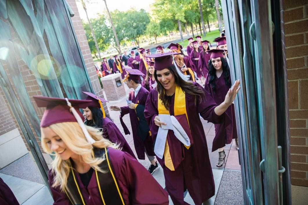 Grads walking through Paley Gates at West campus